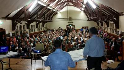 Gary Kent addresses the angry crowd at the overflowing meeting